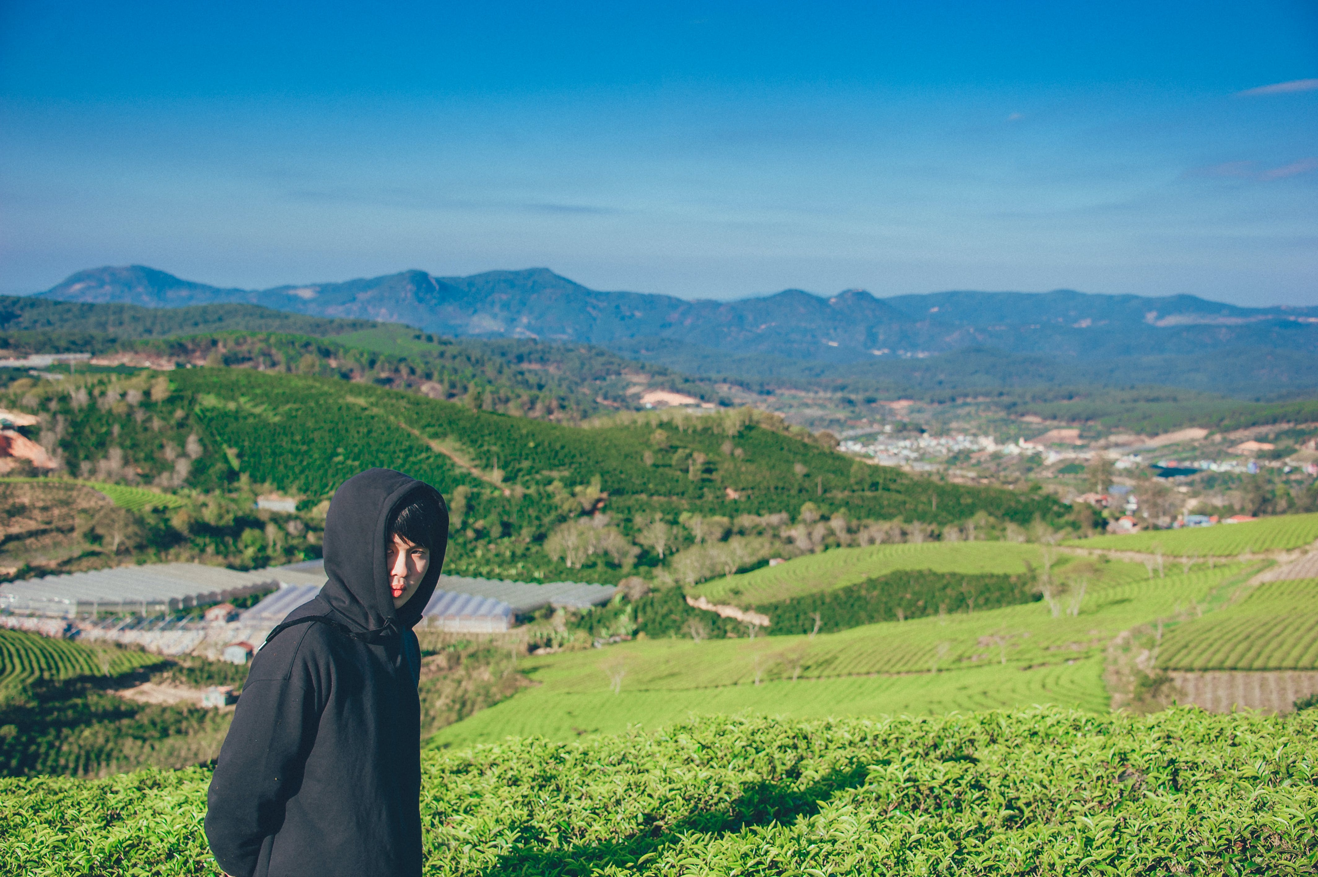 Man Wearing Hoodie Taking Picture With Mountain and Field Photography