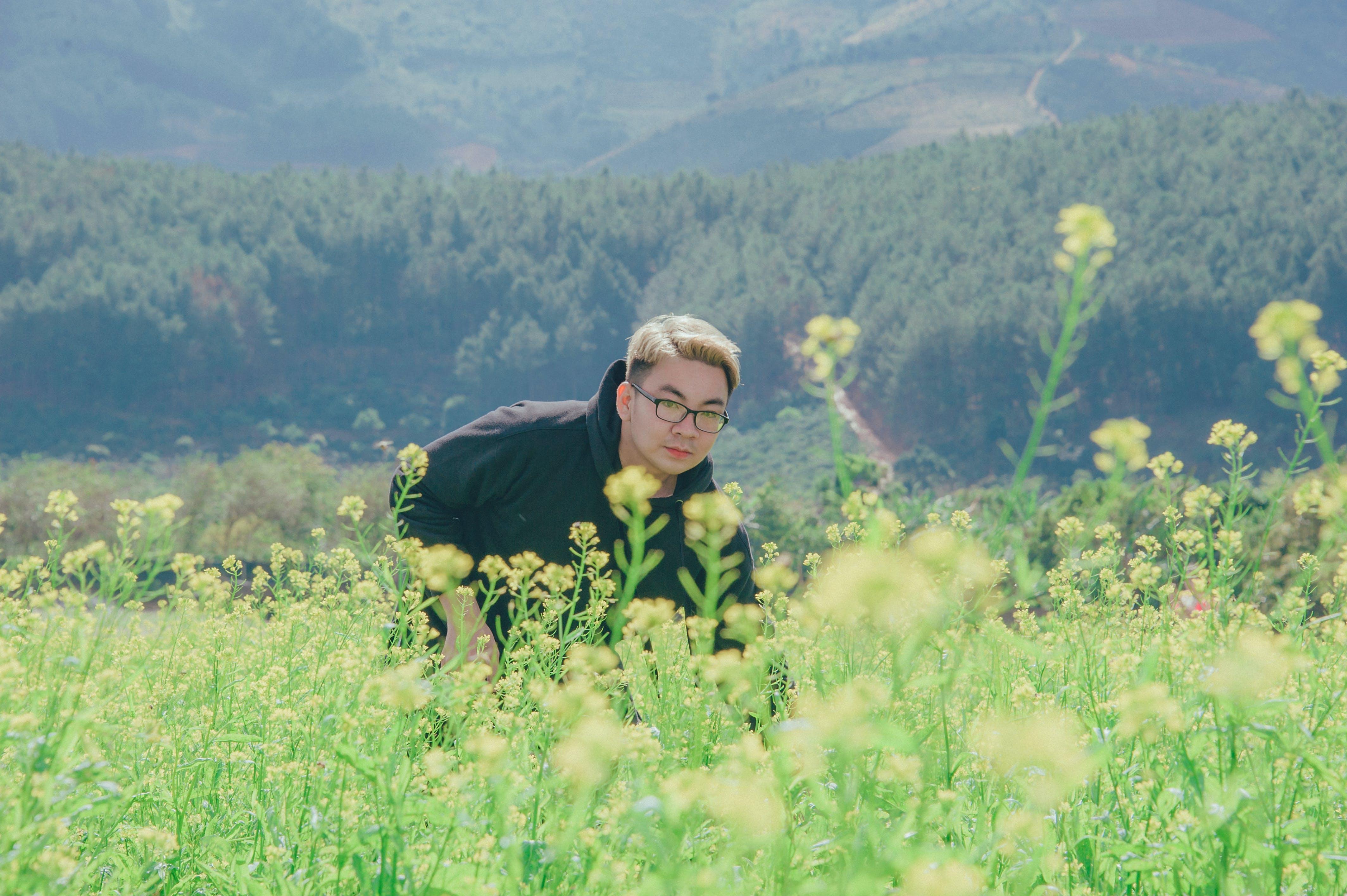 Man in Black Pullover Hoodie Standing in Flower Field