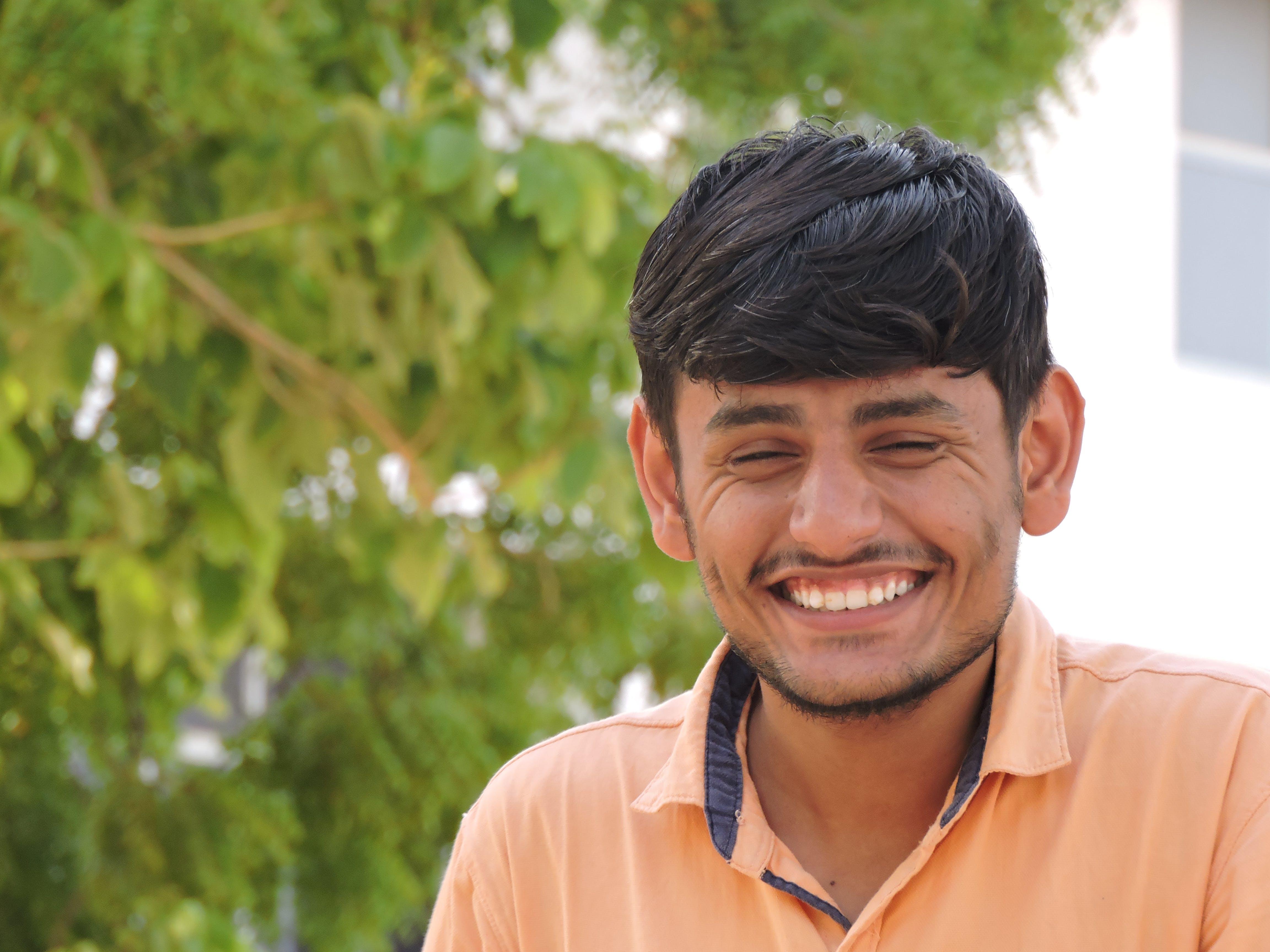 Man Smiles While Taking Photo Near Tall Tree at Daytime