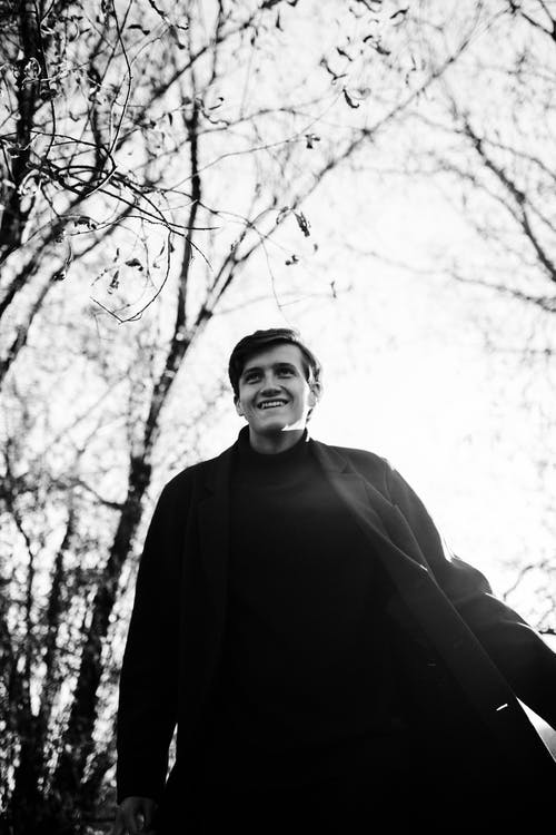 Man in Black Jacket Standing Near Bare Trees