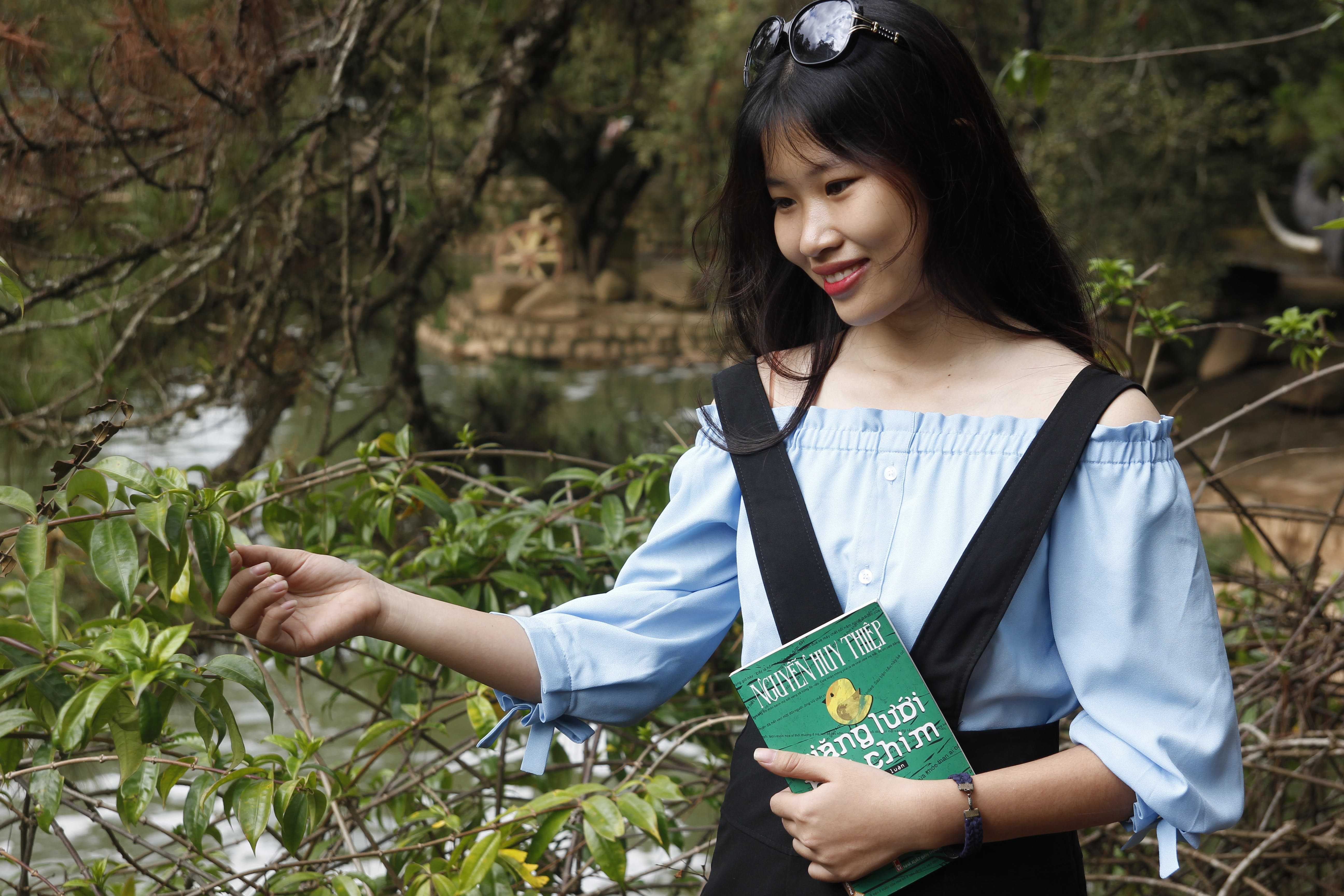 Woman Wearing Blue Off-shoulder Blouse Holding Book Next to Green Leaf Plant