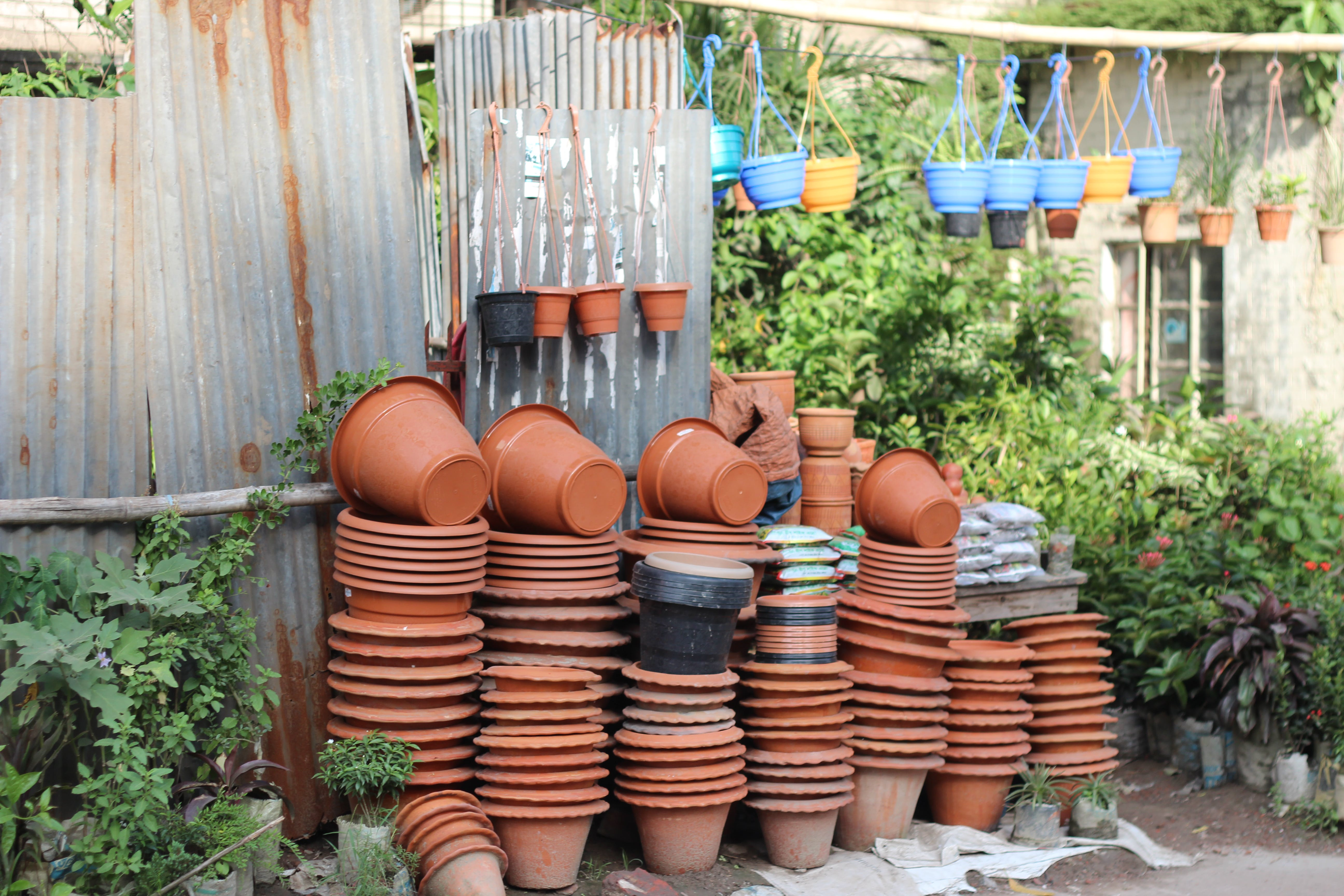 Stack of Clay Pots Beside Tin Roof