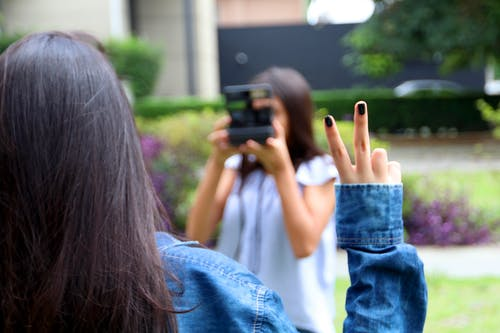 Woman Holding Camera While Taking Picture Of A Woman With A Peace Finger Sign