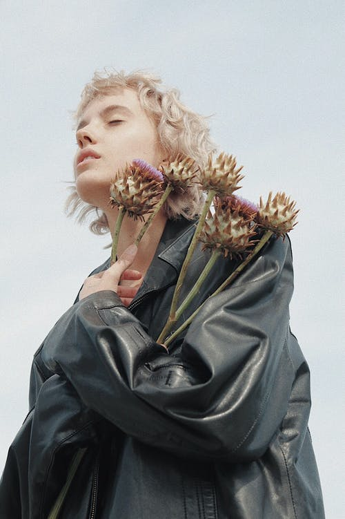Portrait of blond hair woman in leather jacket holding flowers