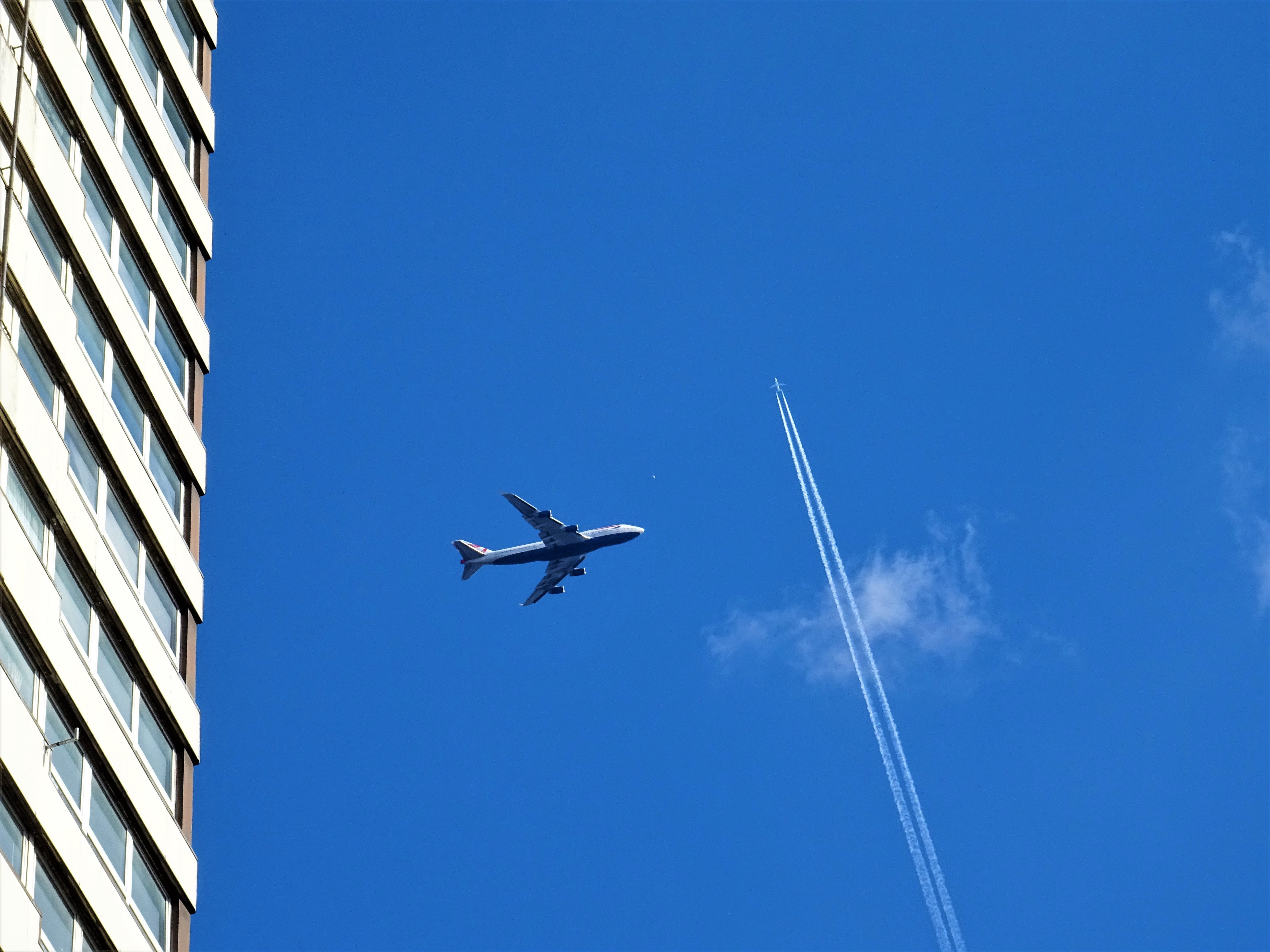 Low-angle Photography of White Plane on Mid-air Near White Concrete Building and White Contrail