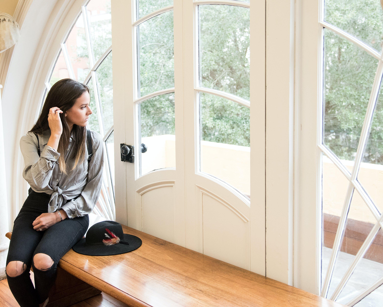 Woman Sitting on Brown Bench Beside Closed Door