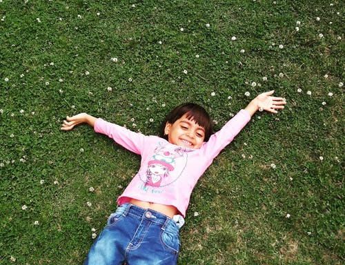 Girl Laying On Green Grass