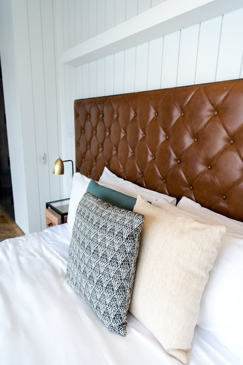 Brown Leather Couch Beside White Pillow