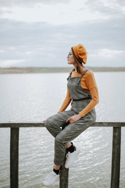 Young woman wearing checkered dungarees and beret admiring landscape