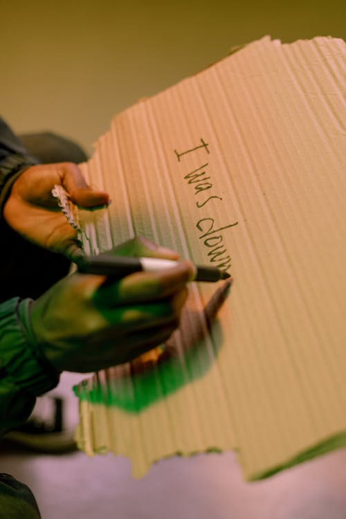 Close-up view of man writing on cardboard
