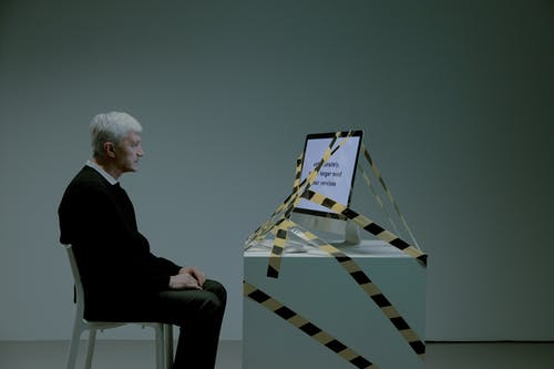 Elder man sitting in front of a computer tied with black and yellow tape