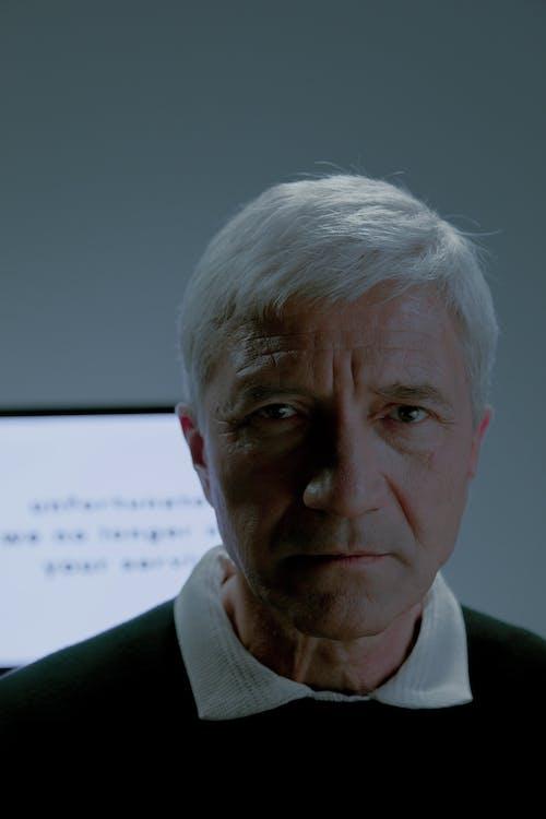 Elderly man and screen behind him