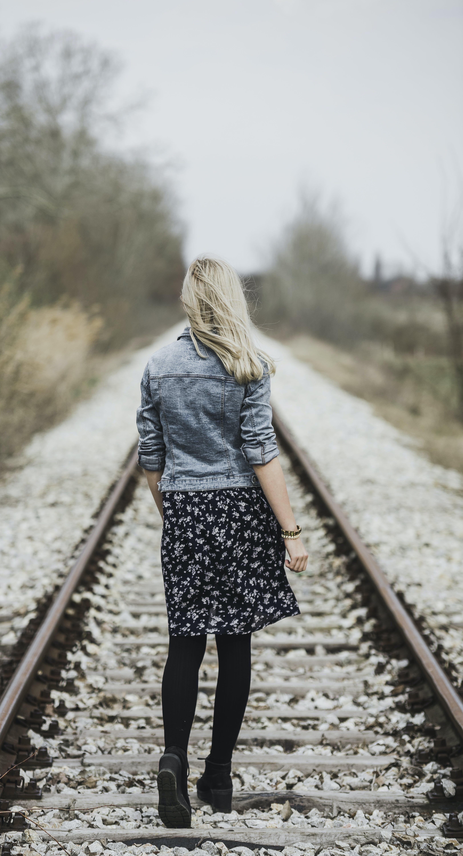 Woman in Blue Denim Jacket, Black Leggings and Black and White Dress Walking on Train Rail