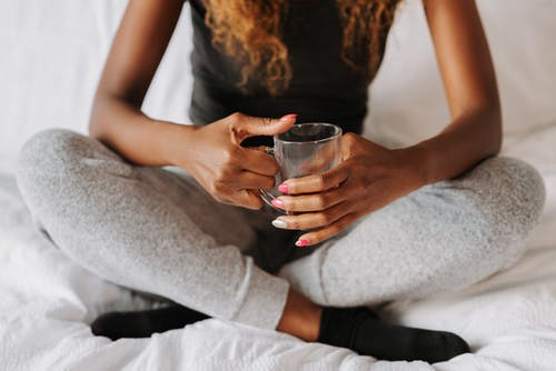 Woman holding drinking glass in bed