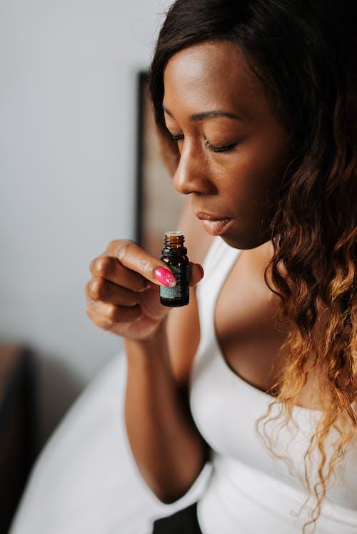Kostnadsfri bild av brunt hår, eterisk olja, flaska