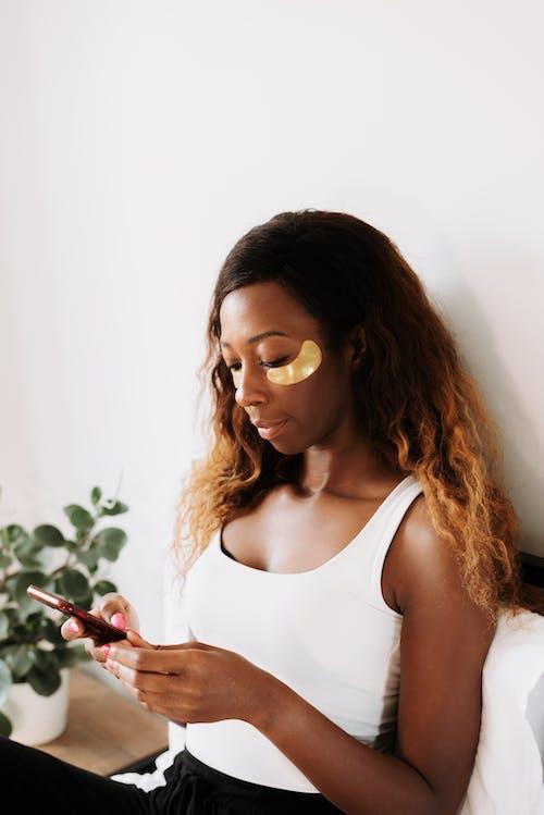 Kostnadsfri bild av ansiktsvård, använder telefon, brunt hår