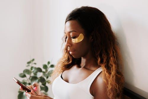 Kostnadsfri bild av ansiktsmask, ansiktsvård, använder telefon