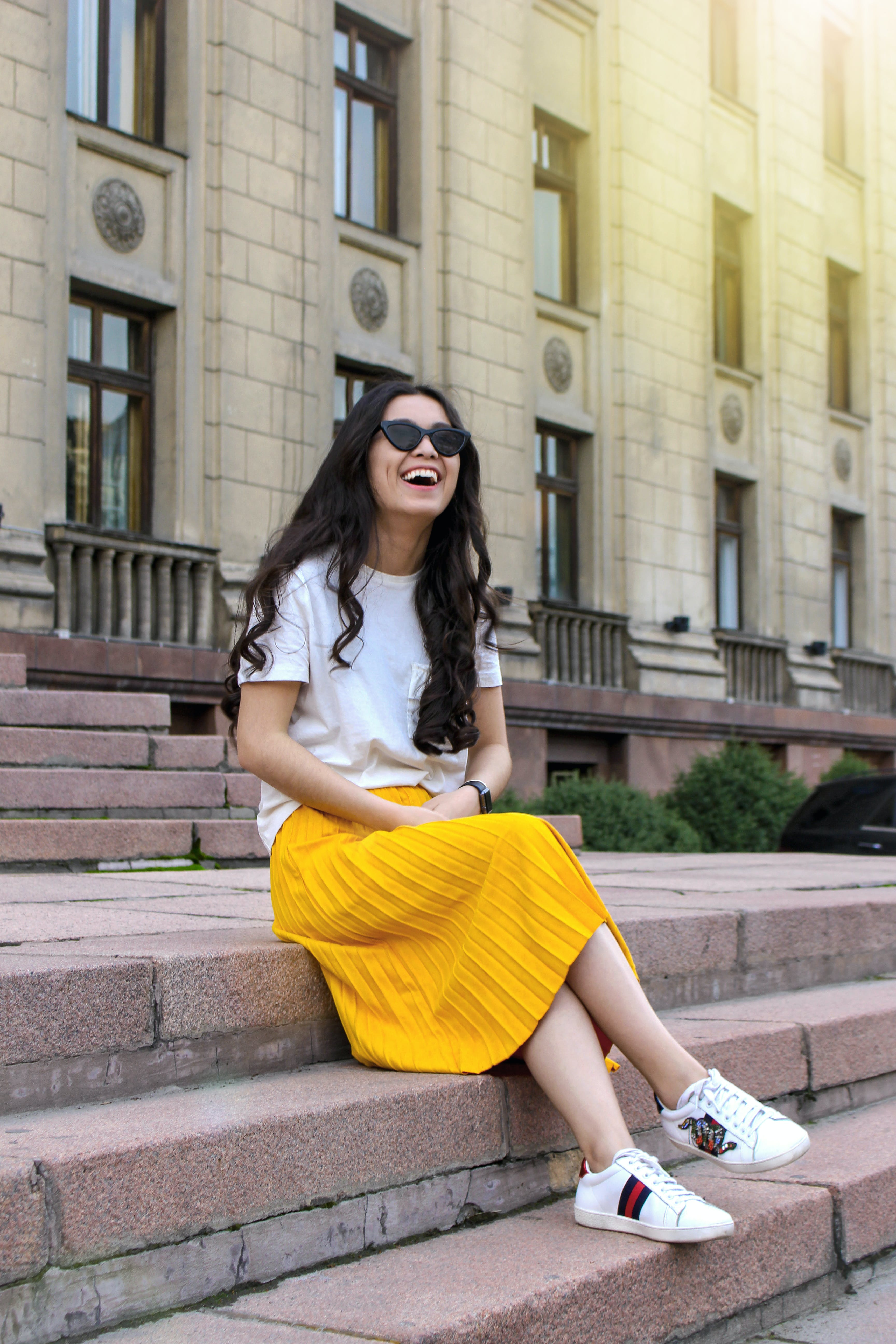 Woman Wearing White Shirt and Yellow Skirt Sitting on Brown Concrete Brick Stairs