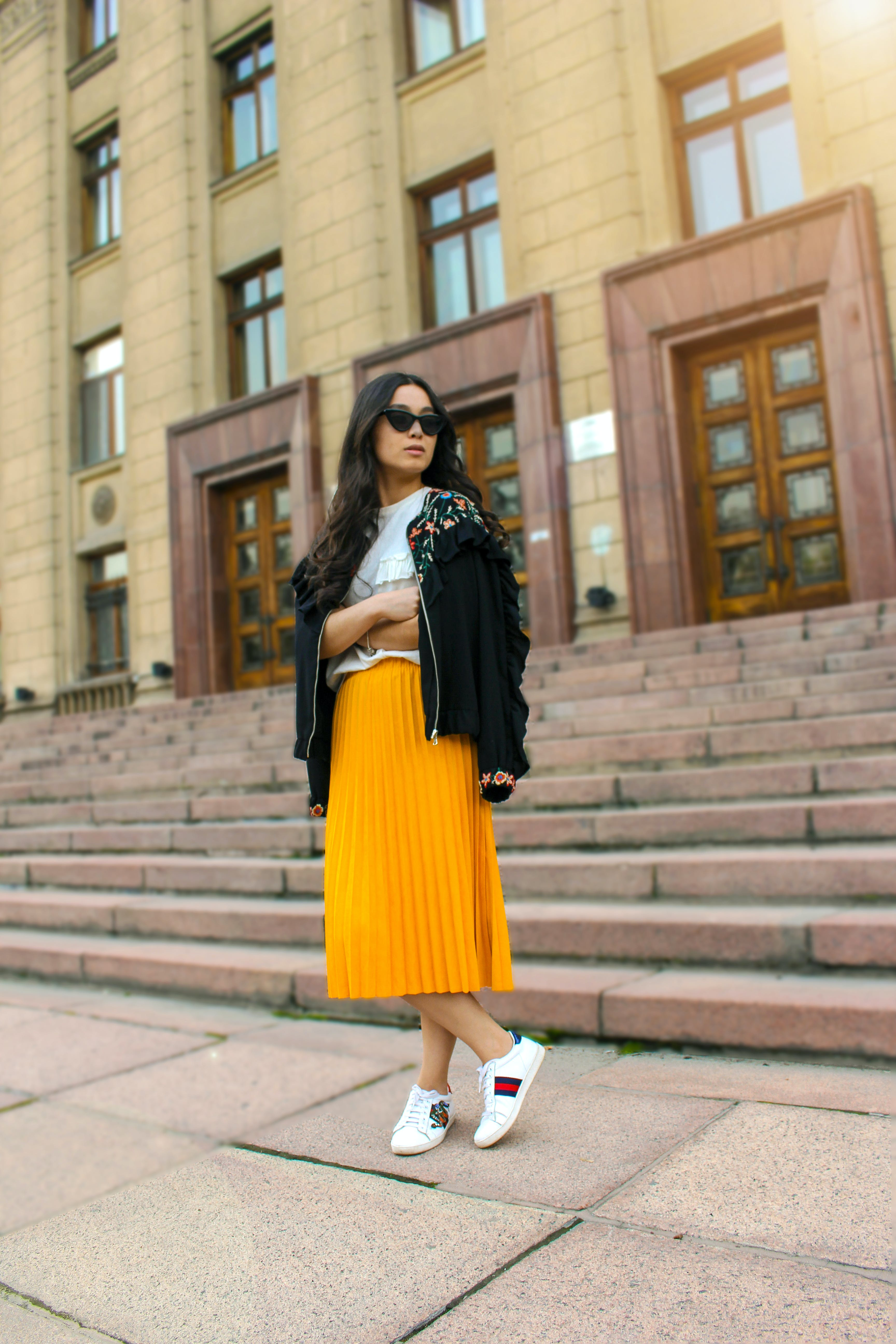 Women Wearing Black Jacket and Pleated Yellow Skirt Standing on Brown Floor