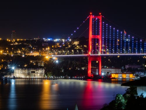 Red Bridge over Body of Water during Night Time