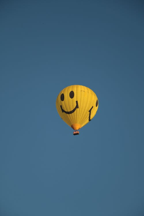 Yellow balloon with smile on clear sky