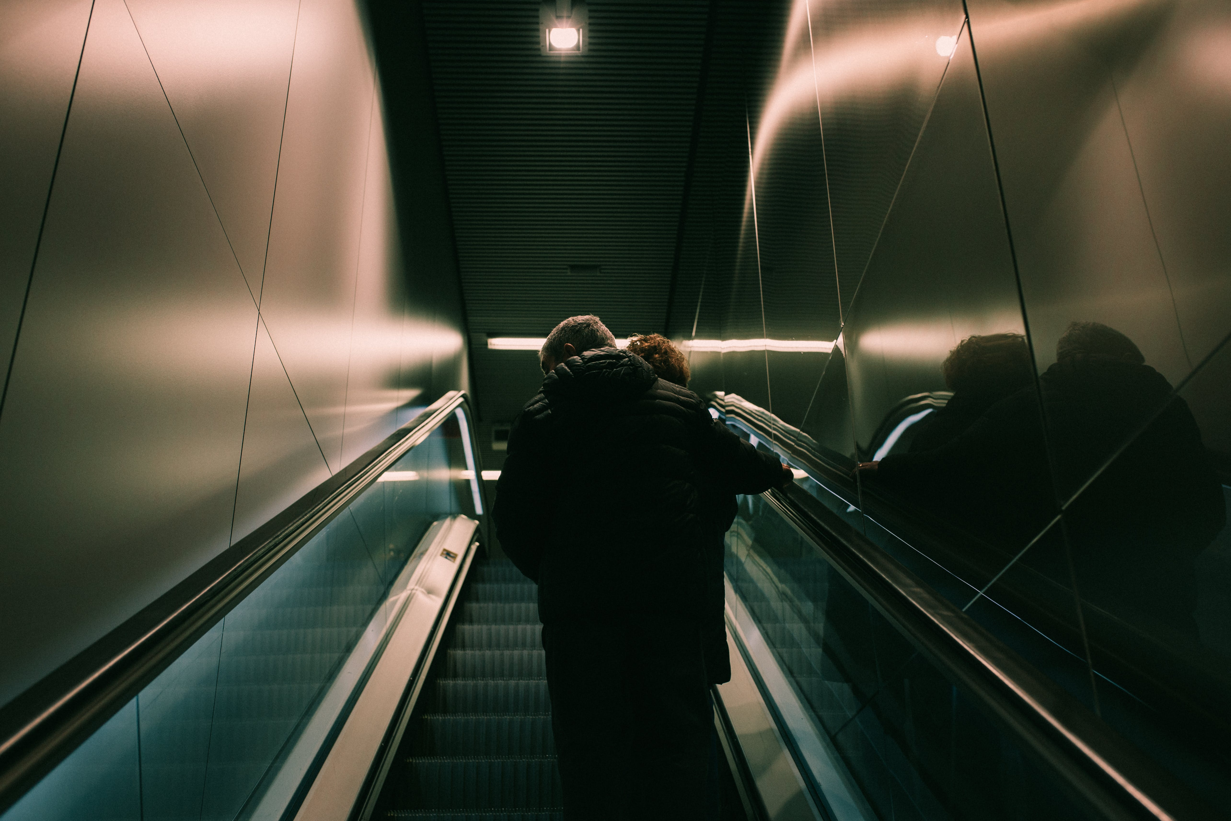 Person in Black Jacket Standing on Escalator
