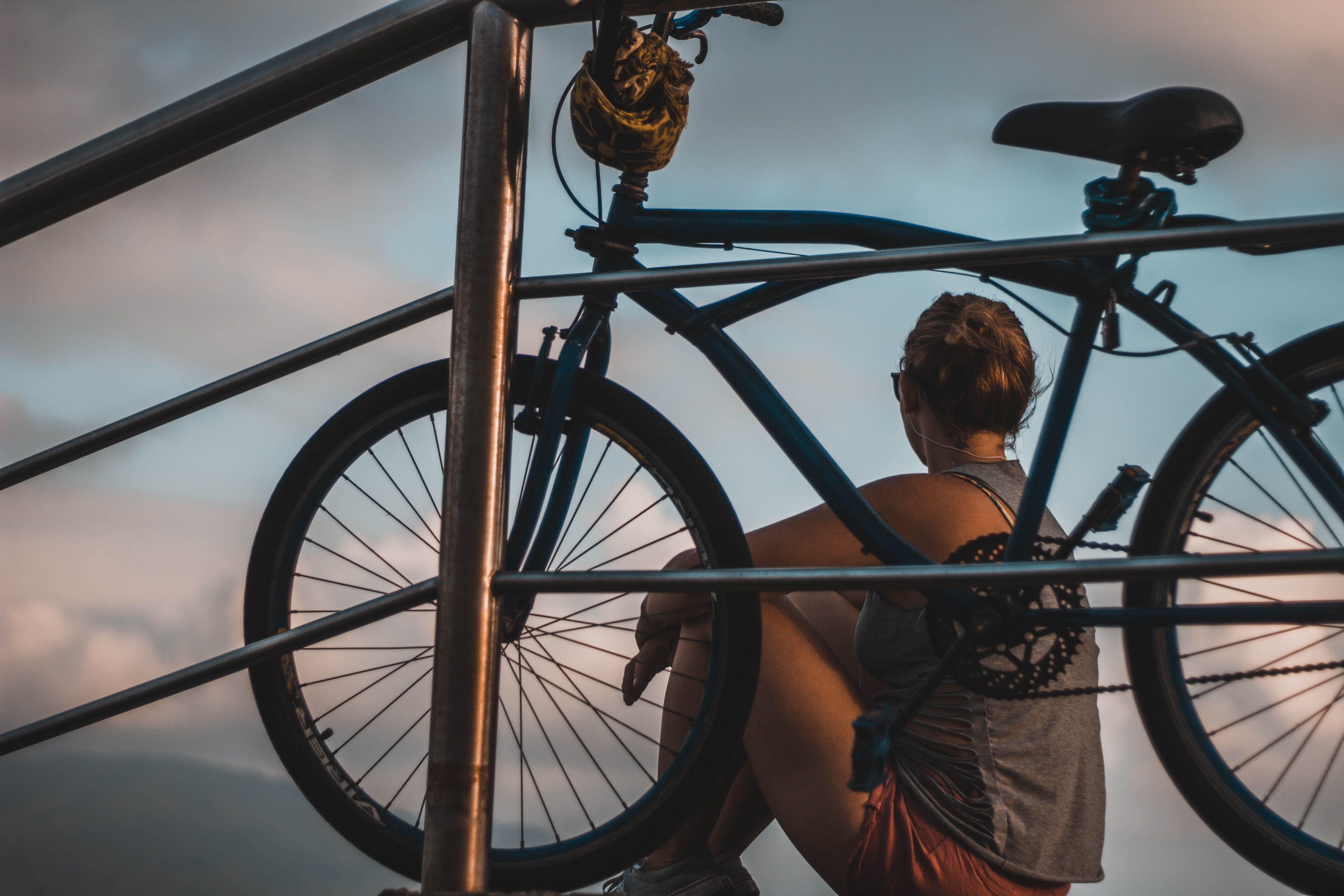 Woman in Gray Tank Top Sitting Beside Black Cruiser Bike