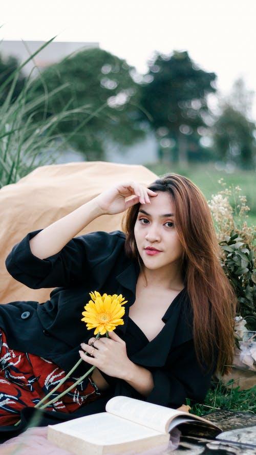 Woman in Black V Neck Long Sleeve Shirt Holding Yellow Flower