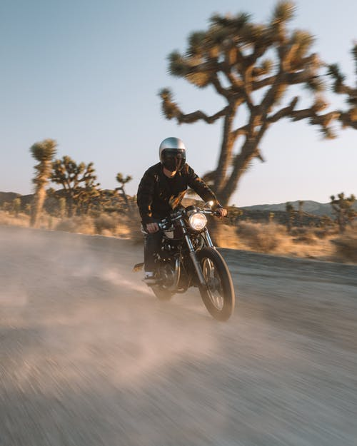 Man in Black Jacket Riding Motorcycle on Road
