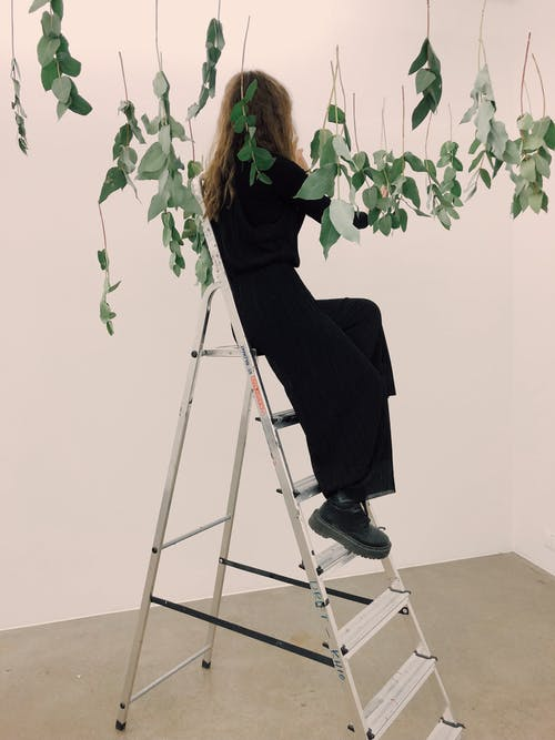 Woman Sitting on Tip of Ladder