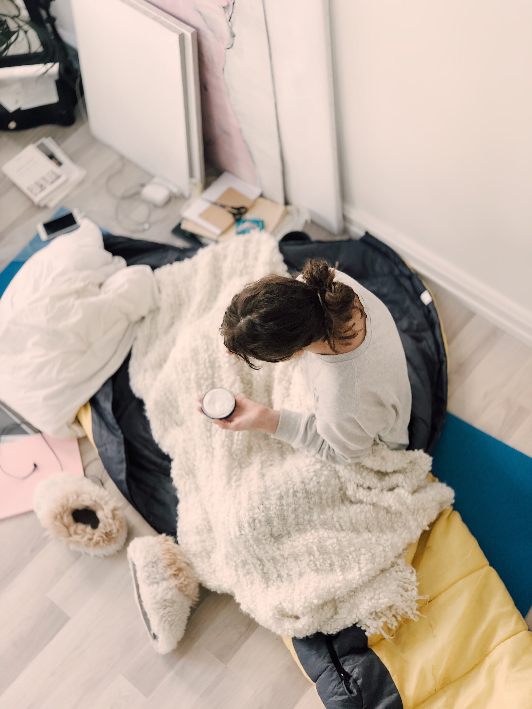 Woman Wearing Sweatshirt Holding Cream Jar