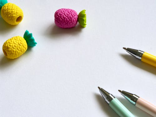 Closeup Photo of Three Assorted-color Pens Near Pineapples Miniatures