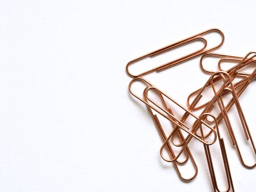 Brass-colored Paper Clips on White Surface