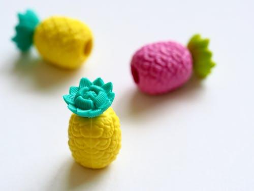 Three Plastic Pineapple Figures on White Surface