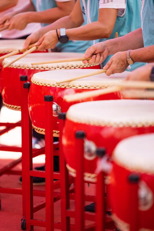Unrecognized drummers standing in row playing red drums