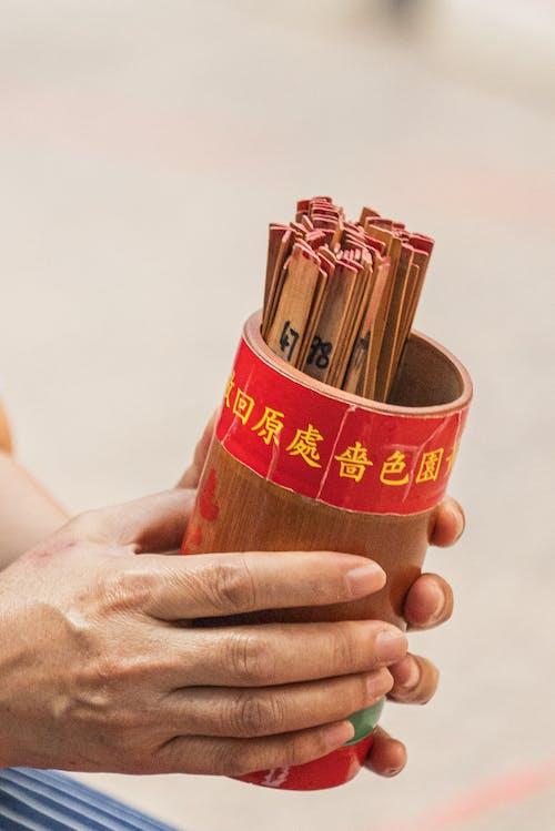 Unrecognizable hands holding Buddhist fortune-telling sticks