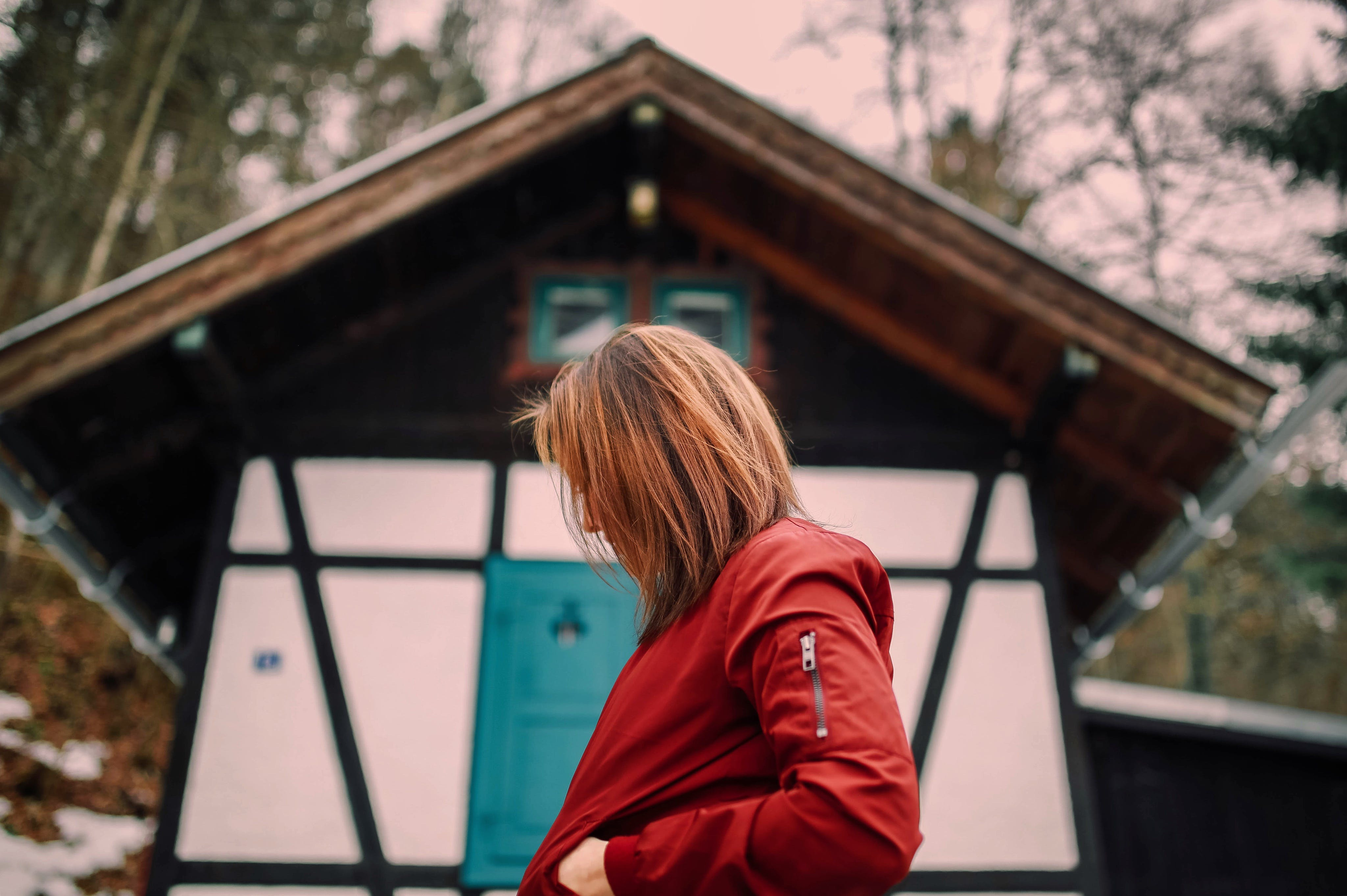Woman in Red Jacket Standing Near Brown and White Wooden House