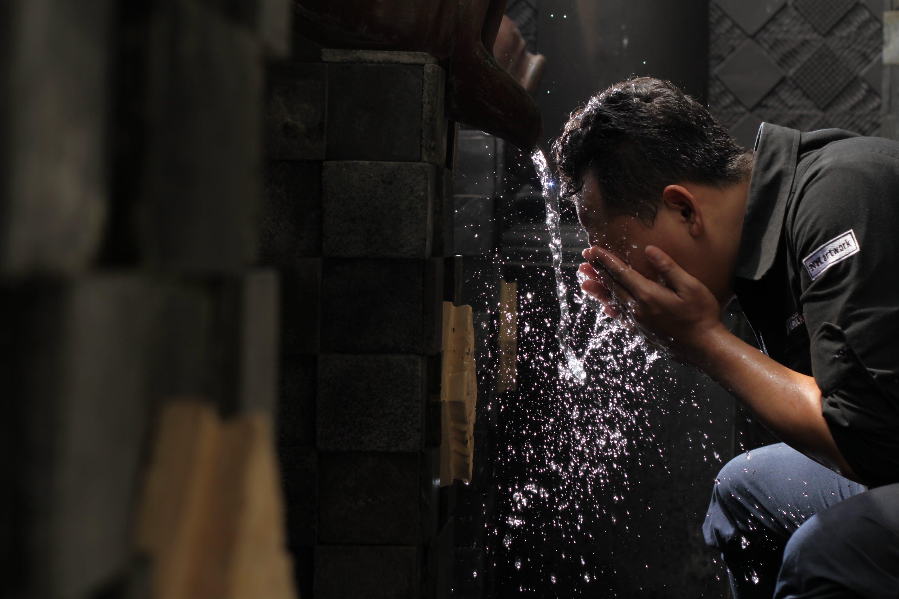Man in Black Shirt Washing His Face