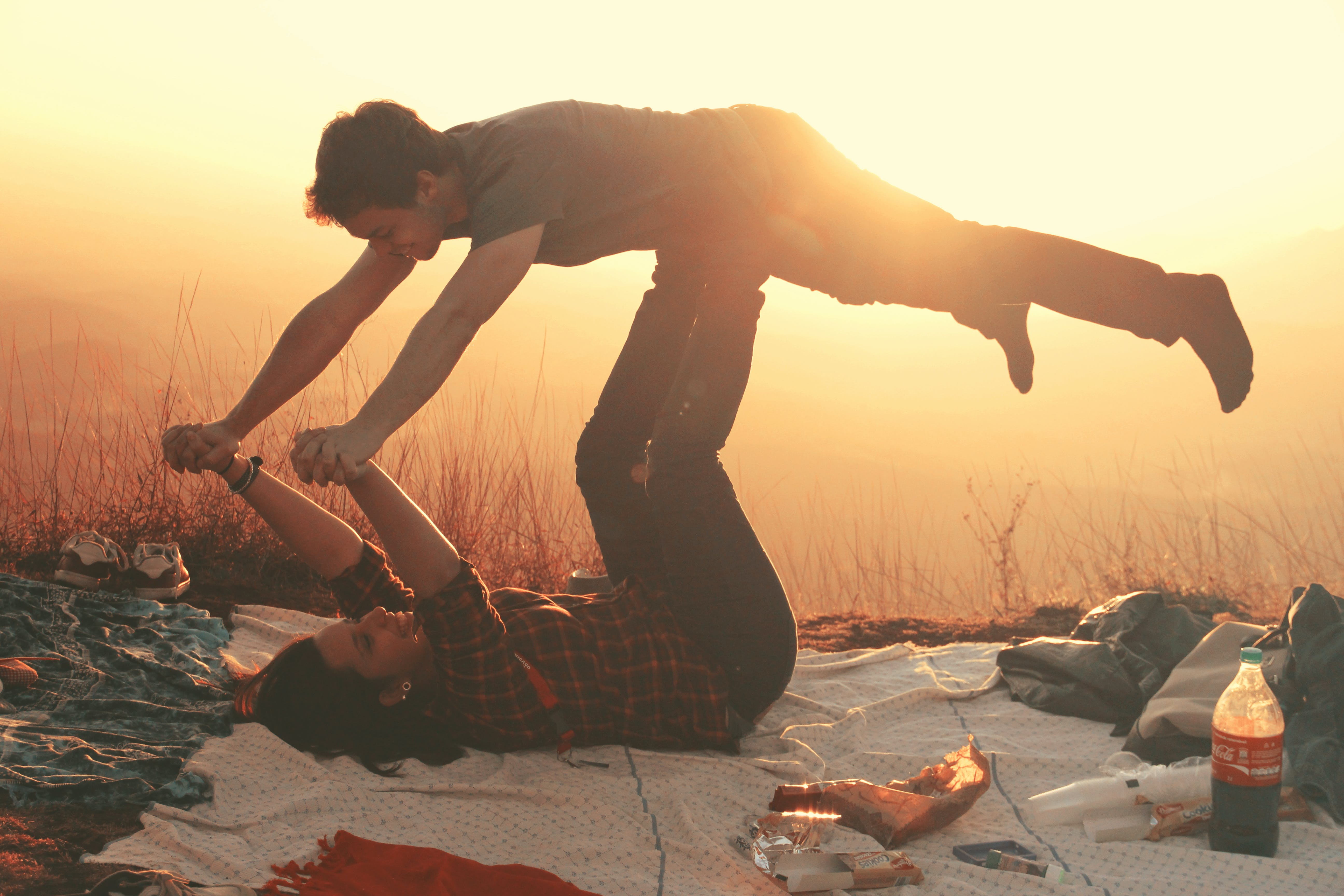 Woman Lying on Blanket Under Man on Her Legs Holding Hands during Golden Hour