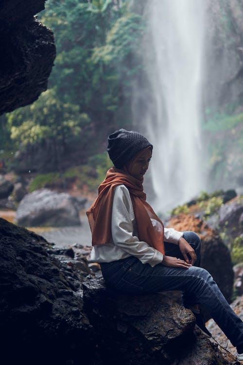 Woman in Orange Jacket and Blue Denim Jeans Sitting on Rock Near Waterfalls