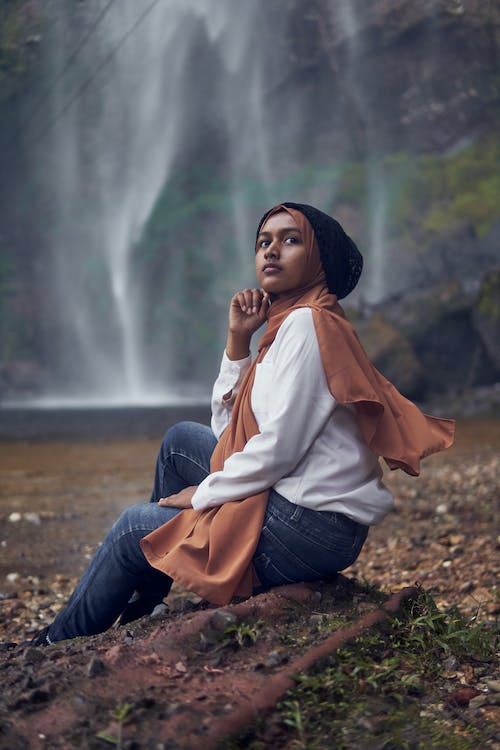 Woman in White Long Sleeve Shirt and Blue Denim Jeans Sitting on Brown Rock Near Waterfalls