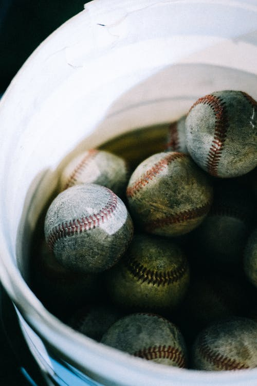 White and Red Baseball on White Round Container