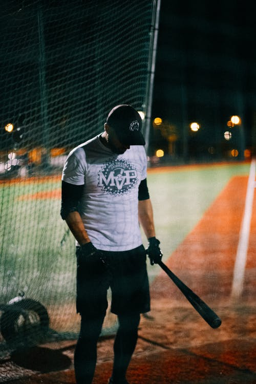 Man in Black and White Crew Neck T-shirt and Black Pants Holding Black Metal Bar