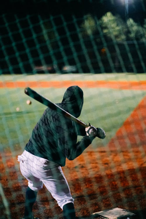 Man in Black Jacket and White Pants Holding Baseball Bat
