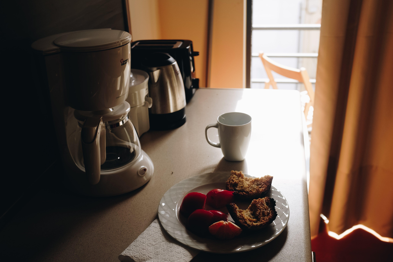 White Ceramic Mug Beside Ceramic Plate On Table