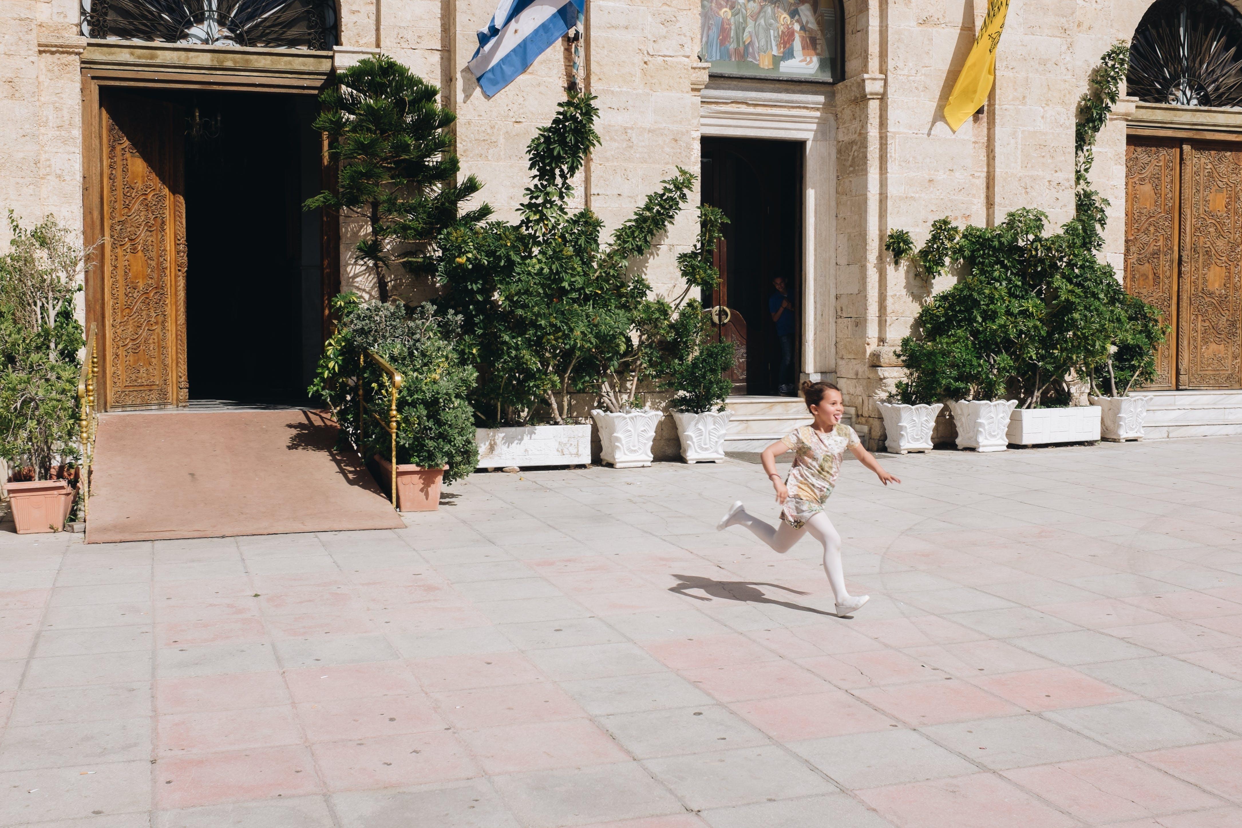 Boy Running on Gray Concrete Floor
