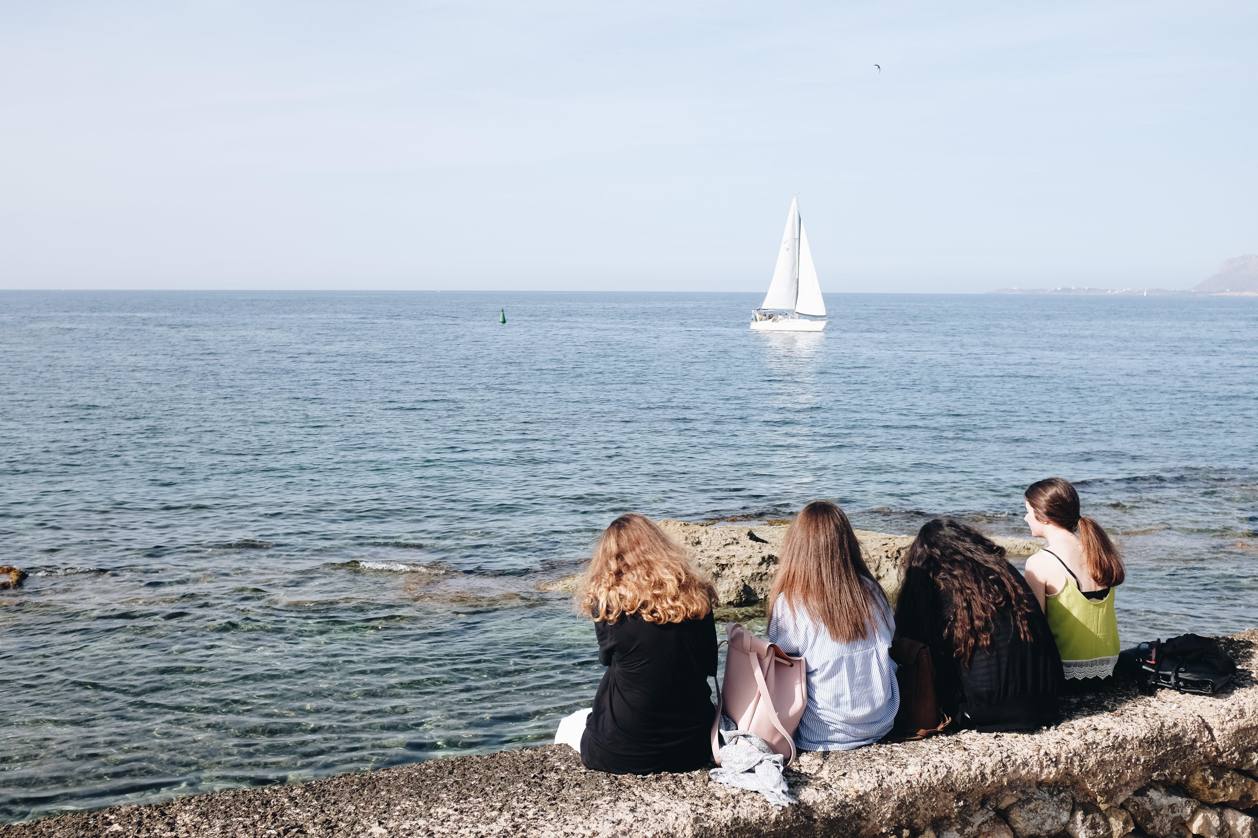 Four Women Sitting Near Sea At Daytime