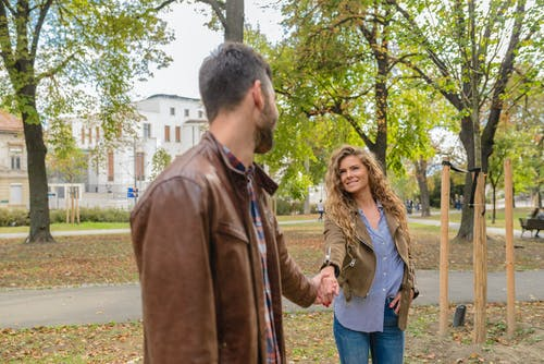 Man Holding Woman's Hand Near Trees
