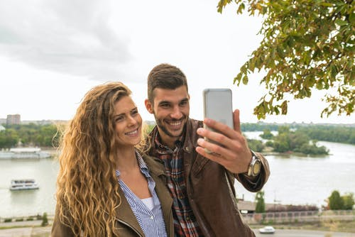 Man Holding Smartphone Beside Woman Near Tree