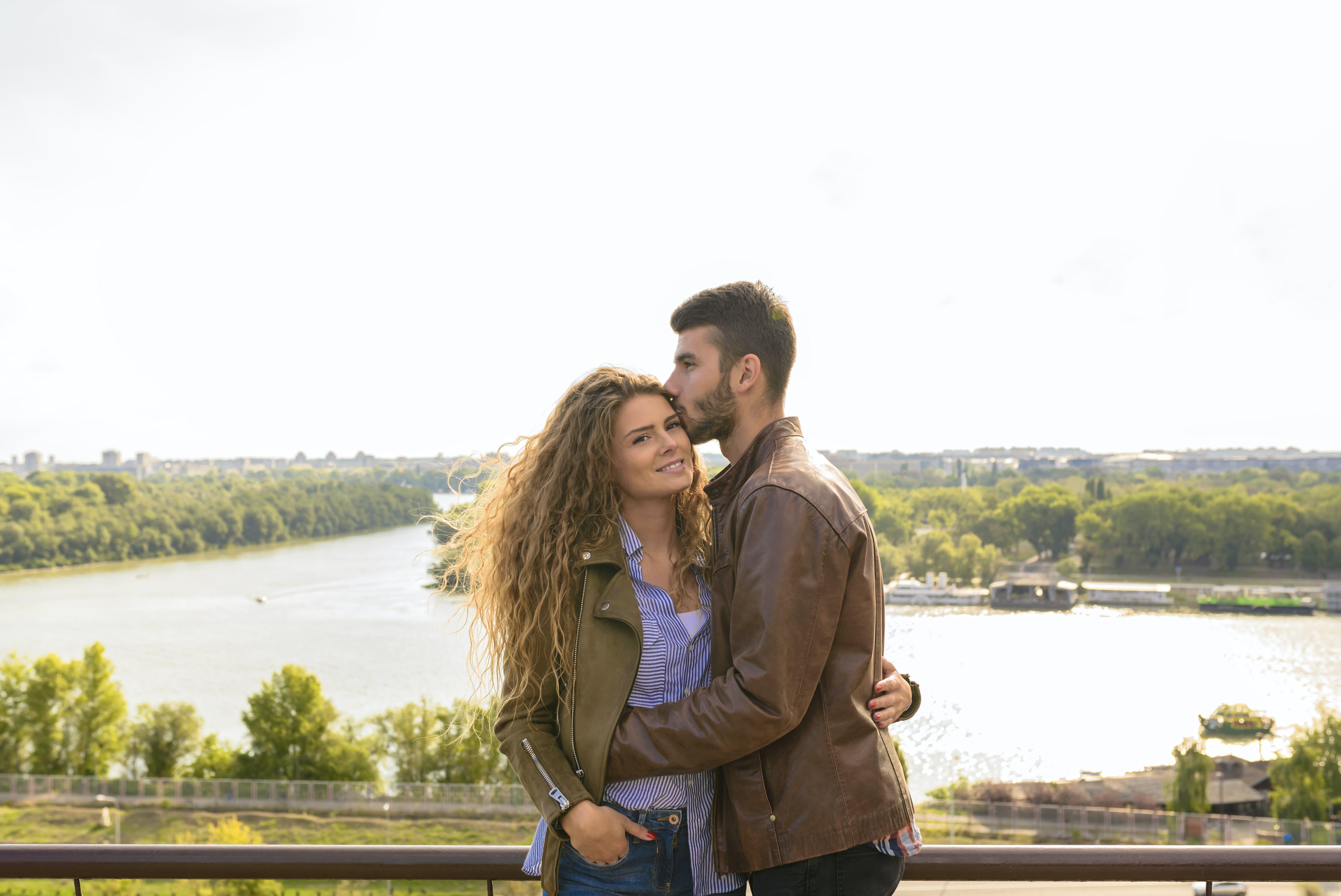 Man Wearing Brown Leather Jacket Hugging Woman Wearing Brown Zip-up Leather Jacket